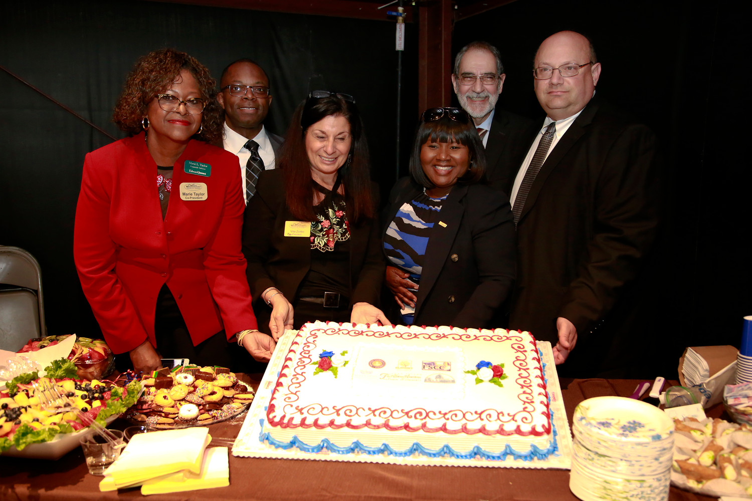 Marie Taylor, left, Dennis Jones, Vita Zorbo, Valerie Anderson Campbell, Paul Sapienze and Bruno Caracciolo cut the cake.