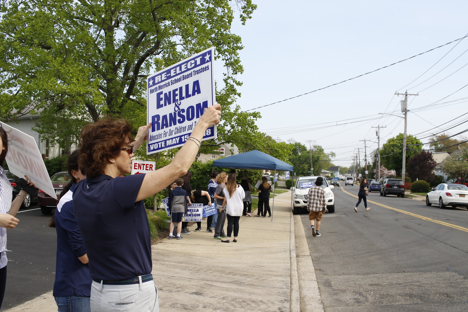 Supporters of incumbents Steve Enella and Todd Ransom, Pat Kaplan and her daughter Brooke, waved signs at cars and passersby as they entered the North Merrick Library. Enella and Ransom were defeated by newcomers Vincent Lentini and Michelle Gordon.
