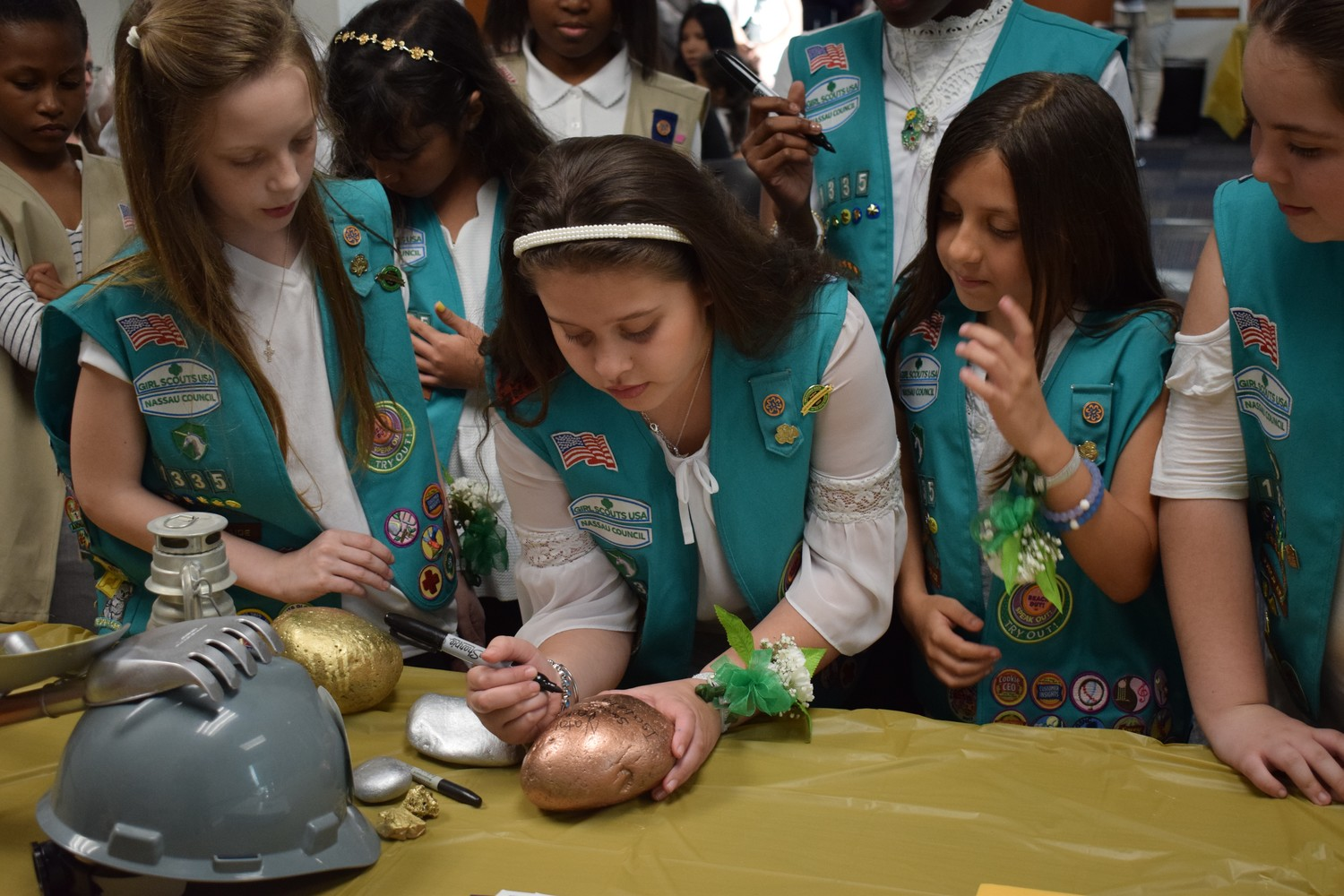 Junior Girl Scouts huddled around the Bronze Rock to sign their names and accept their status as award recipients.