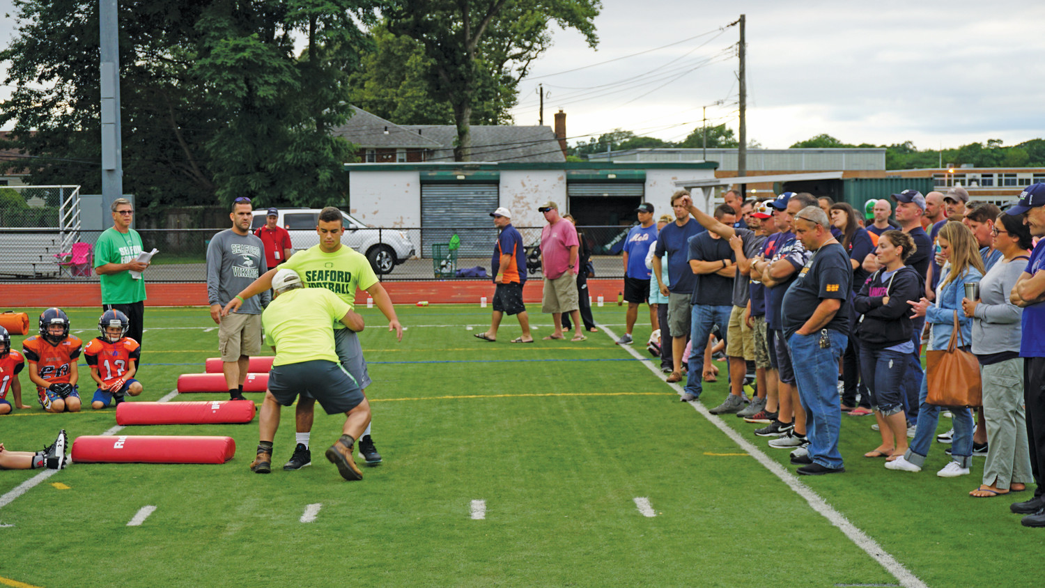 Long Island Broncos players and their parents watched as two Seaford High School varsity football players demonstrated proper tackling.