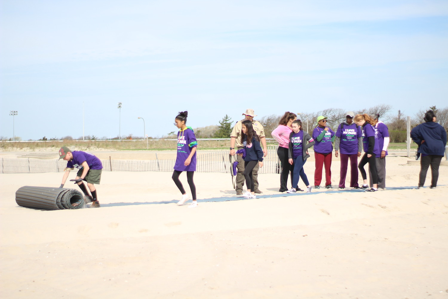 Volunteers at Jones Beach Park rolled out beach access mats, which are used to help disabled beachgoers get closer to the shoreline, as a part of I Love My Park Day.