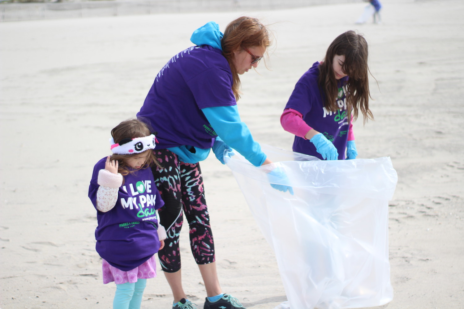 Cathy Kassimatis, of Wantagh, helps her 10-year-old daughter Emily pick up litter at Jones Beach while her other daughter Jeana, 3, looks for more trash.