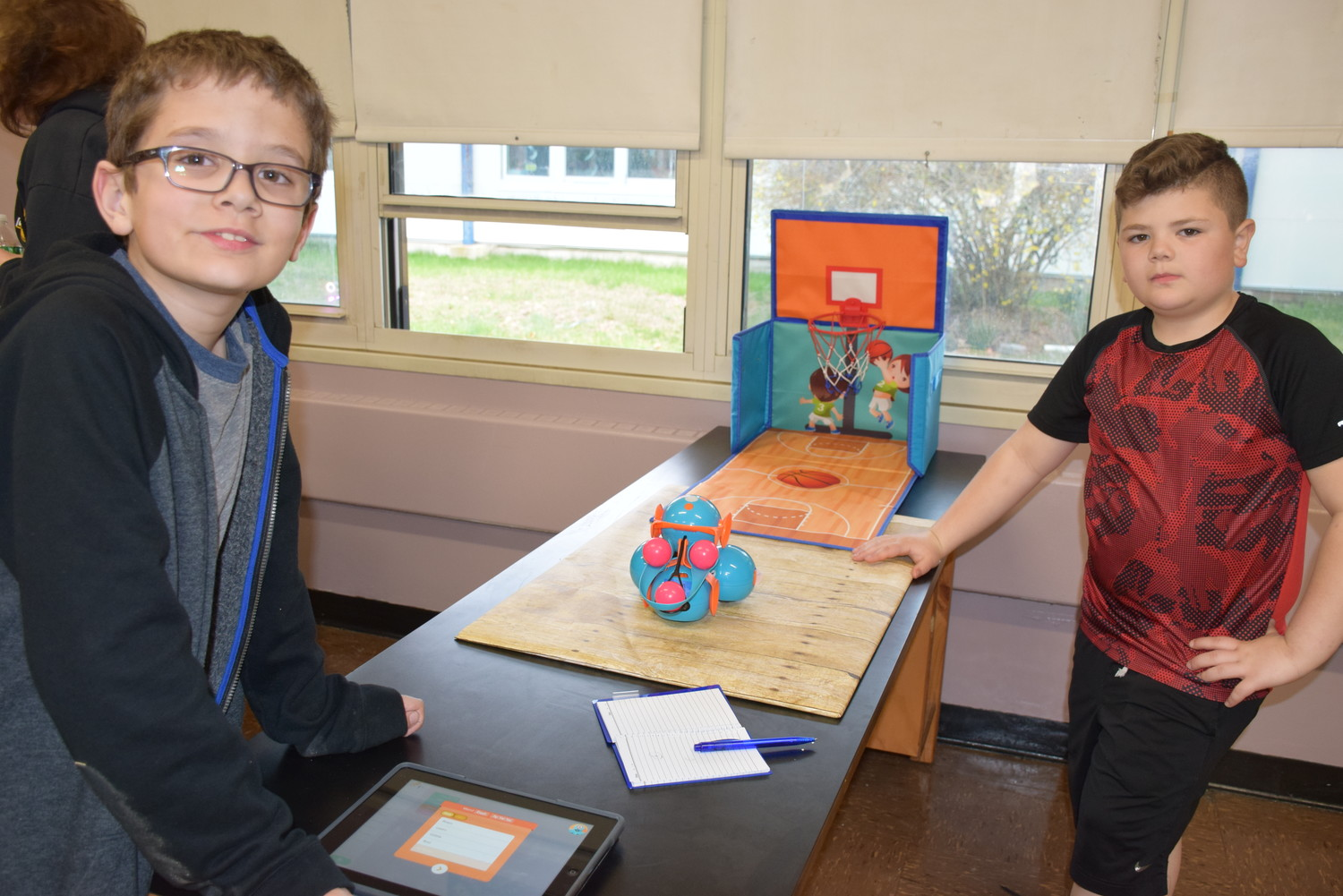 Fifth-grader Gregory Heym, left, and third-grader Joe Divella shoot some hoops by coding robots to take free throws for them.