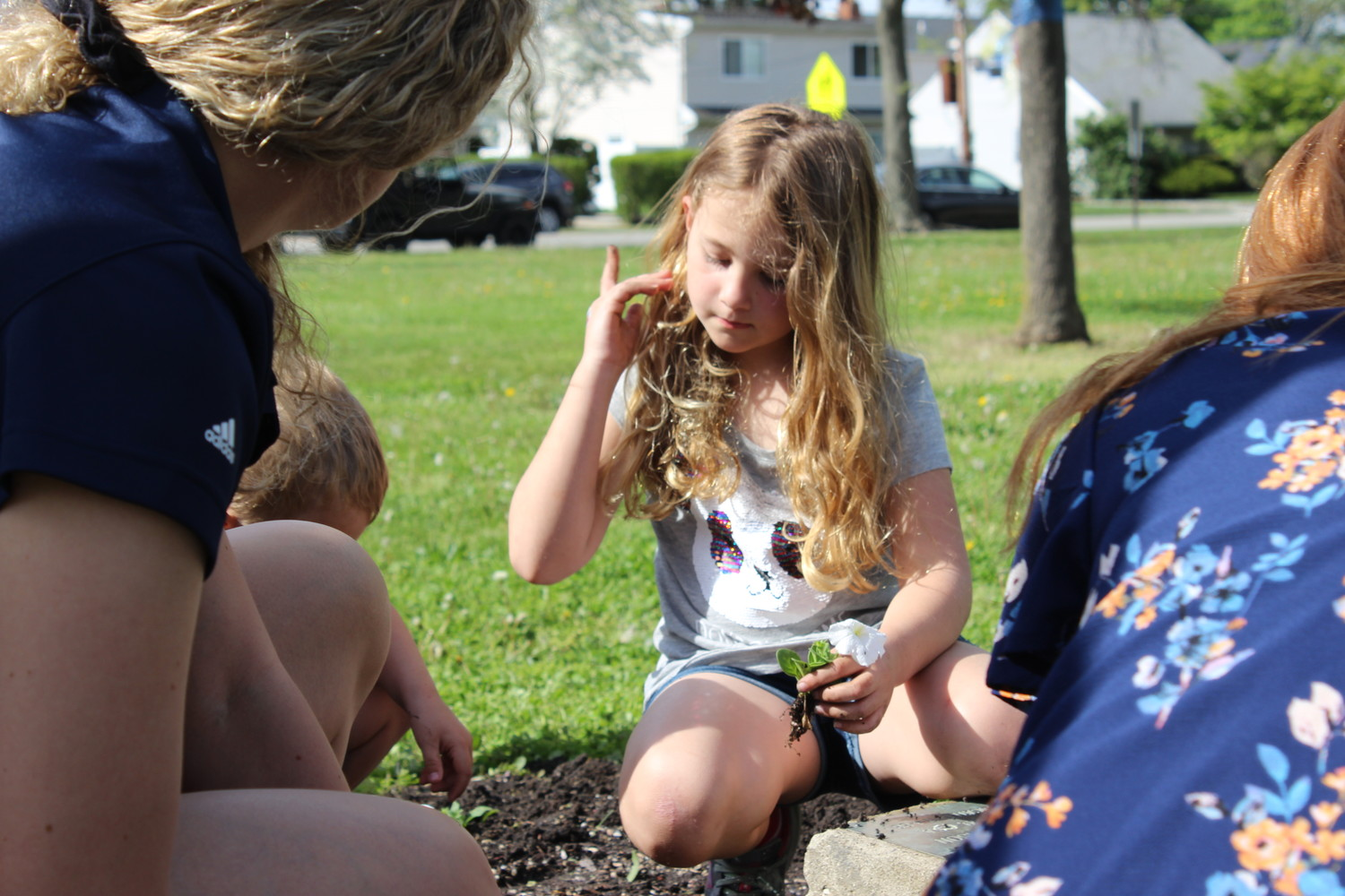 Ella Gorlasky, a second-grade student at Bowling Green Elementary School, marveled at white spring flowers and she planted them in the dirt.