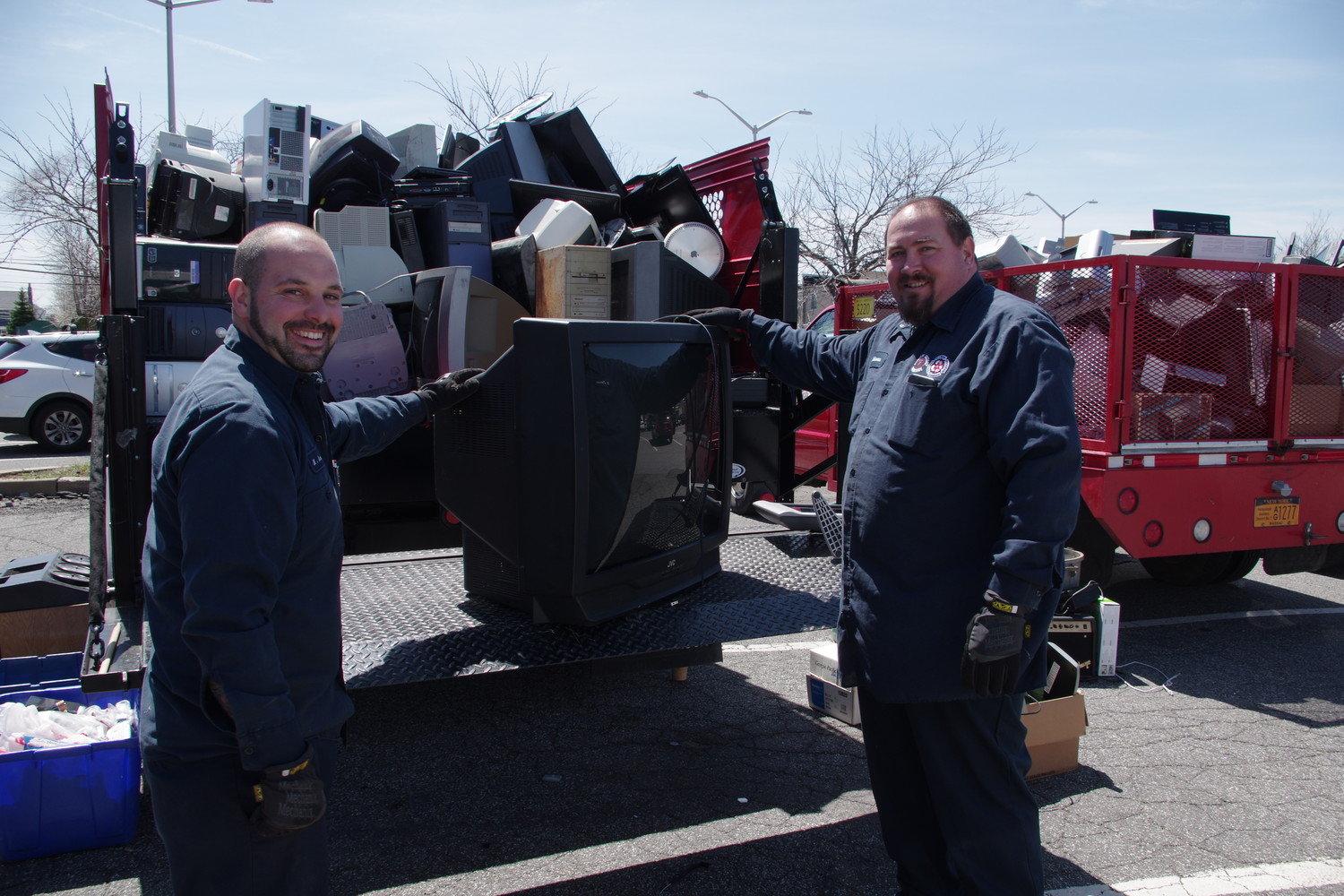 Sanitation workers David Johnson, left, and Matthew Amato loaded an old CRT television to be recycled.