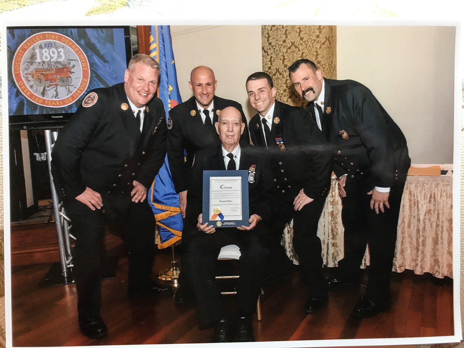 Chiefs of the LVFD congratulated Pat Eliseo, center, for 66 years of service at the Metropolitan in Glen Cove, above.