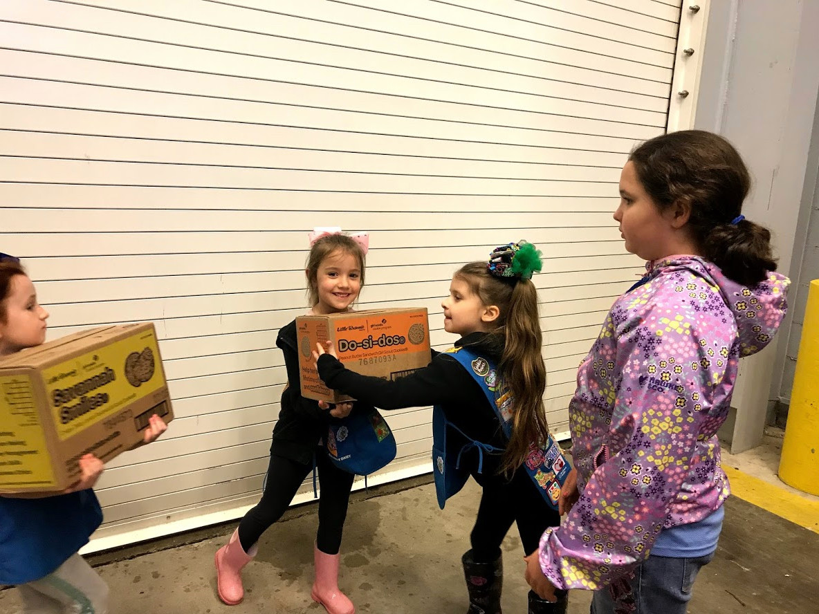 Girl Scout Daisies Valentina Keith, left, hands off a box of Girl Scout cookies — Do-si-dos — to Aliyah Johnson at the United States Coast Guard station in Jones Beach on May 16. The treats were intended for the United States Coast Guard members.