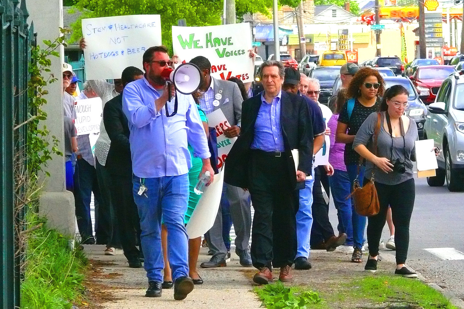Matthew Sexton, with bullhorn, and attorney Norman Siegel, center, lead marchers along Hempstead Turnpike in Sunday's demonstration against the Belmont Park Arena.