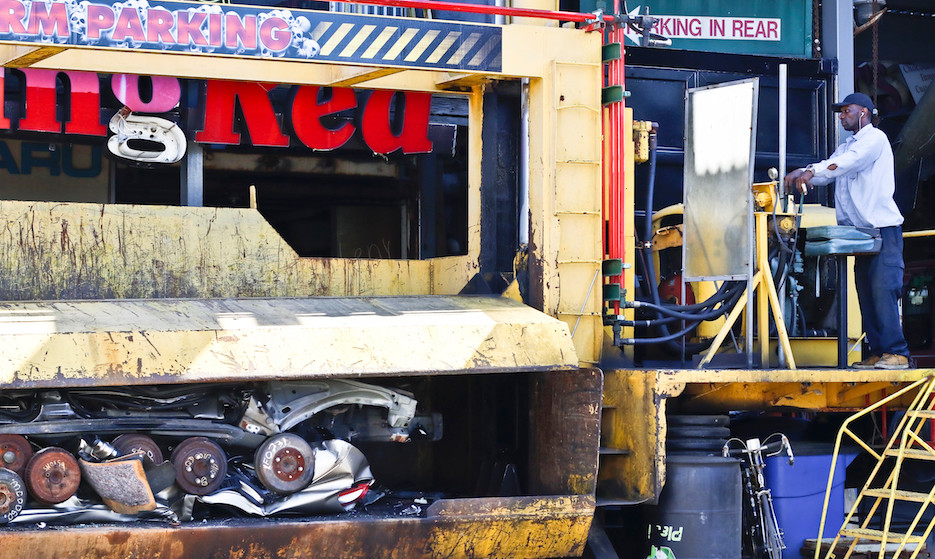 Charles Jones works the crusher to turn a 4 door sedan into a metal pile about a foot hight.