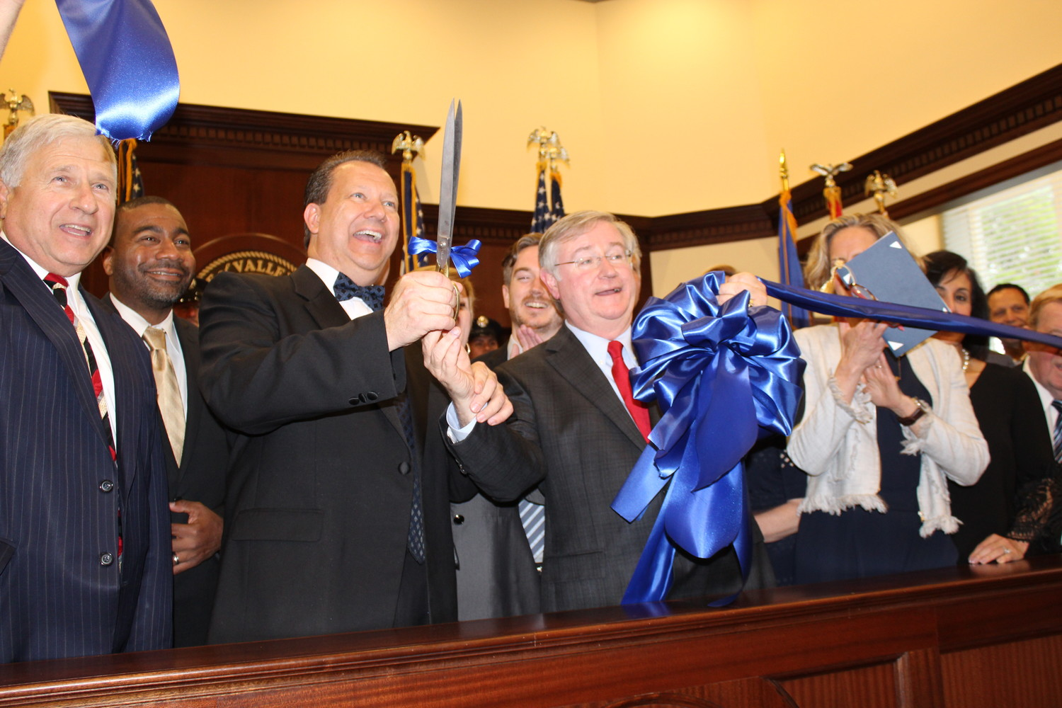 Mayor Ed Fare, center, and Former Valley Stream Village Justice Robert Bogle, right, cut the ribbon for the new courthouse and municipal building on May 16.