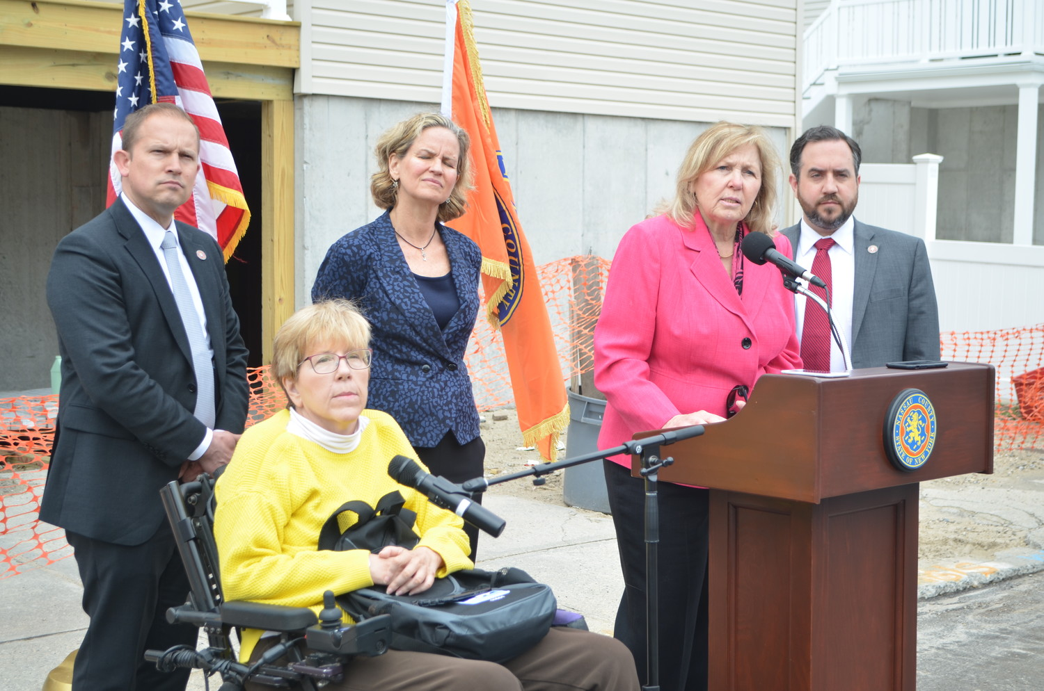 Nassau County Legislator Denise Ford, at lectern, was joined by other county officials on May 14 outside West End resident Liz Treston's Hurricane Sandy-damaged home to urge those who believe they have been victims of contractor fraud to file their cases with the county's Office of Consumer Affairs.