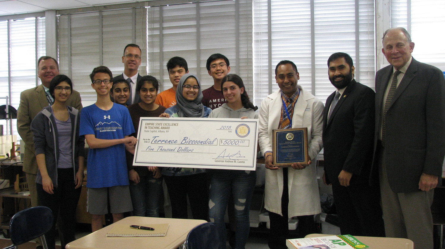 Dr. Terrence Bissondial, the Hewlett High School science teacher who manages the district's science research program, was presented with an Empire State Excellence in Teaching Award. From left were Superintendent Dr. Ralph Marino Jr., Maya Tariq, David Durdaller, Pashma Sadiq, Science Chairman Dr. Brian Terry, Shanzeh Sadiq, Asma Rasheed, Lauren Ledon, Alex Tang, Randel Placino, Bissondial, Governor's Nassau County representative Imran Ansari, and interim high school Principal Jack Lenson.