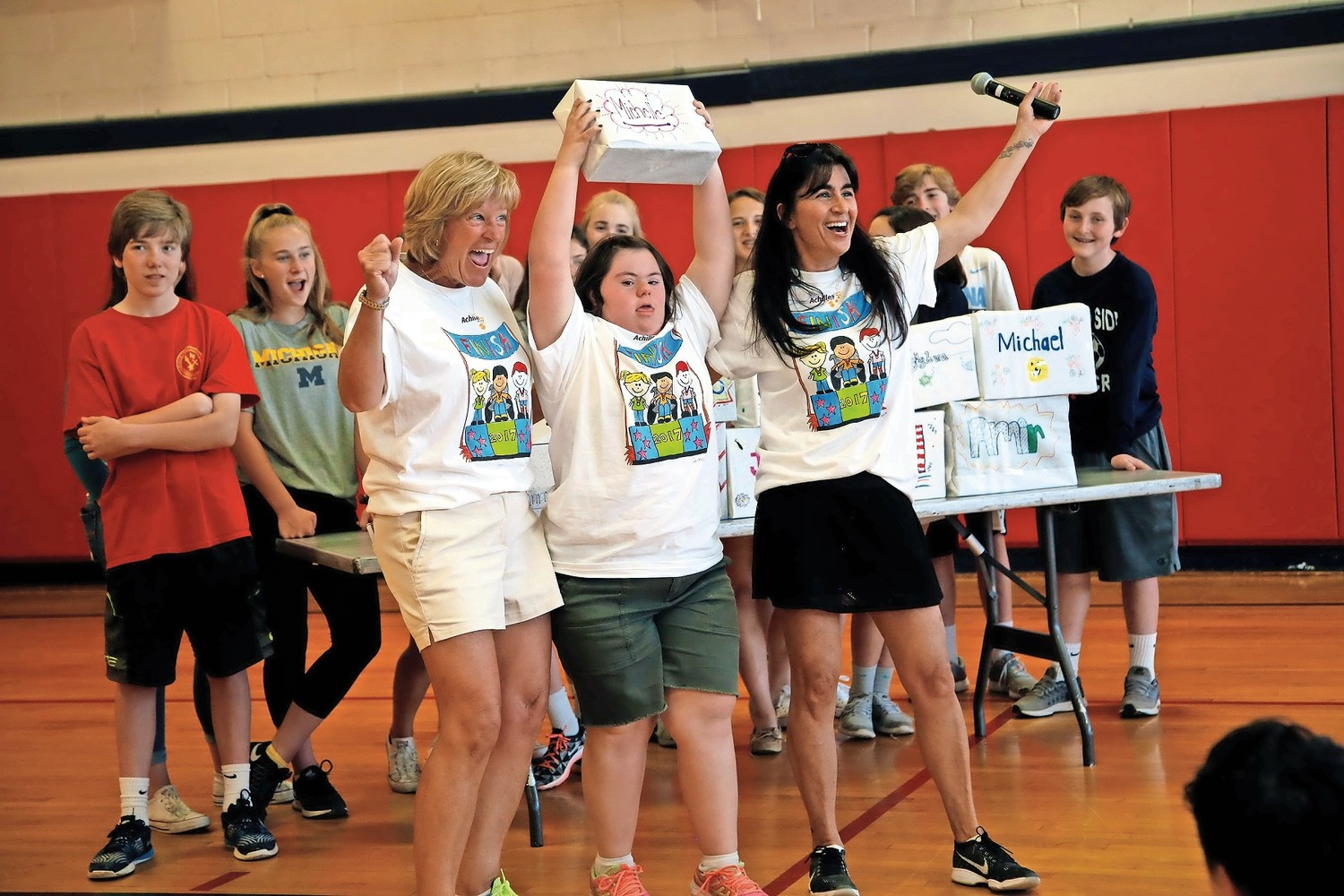 Michelle Piccone, center, with physical education teachers Meaghan Healey and Carolyn Ferguson, raised her sneakers with pride after completing the virtual marathon last year.
