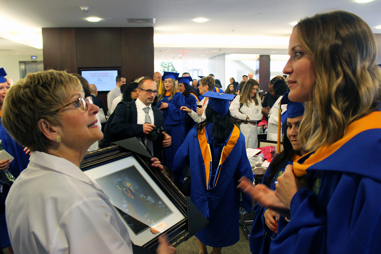 "Dean Kathleen Gallo, left, described her students as ""trailblazers"" for their work in Hofstra's first graduate nursing program. To show her gratitude, Tara Hertz painted the dean a portrait of one of those trailblazers."
