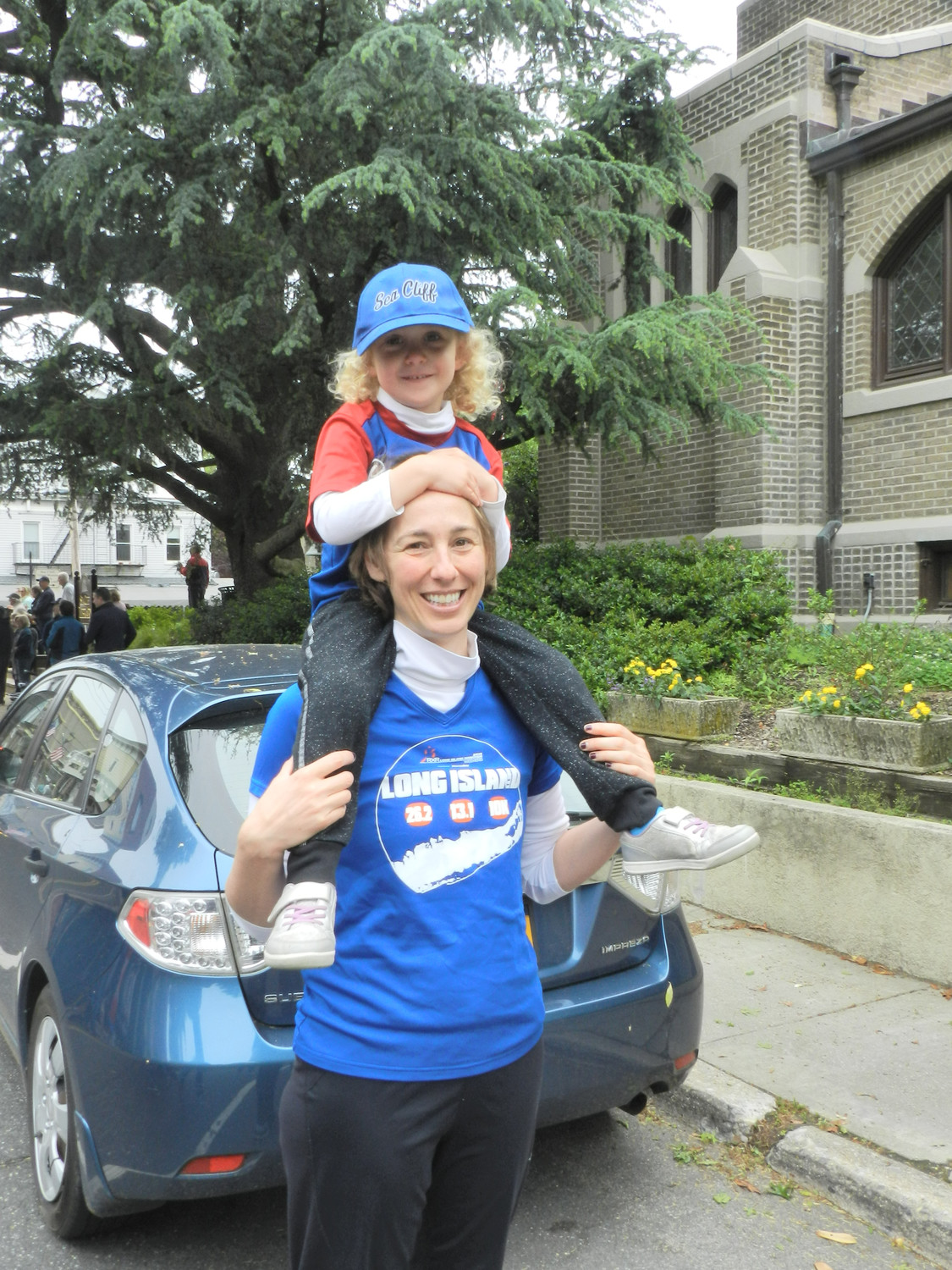 Resident Liz Baron gave her daughter Genevieve, 4, a boost so she could see among the crowds that gathered on Sea Cliff Avenue for the parade.