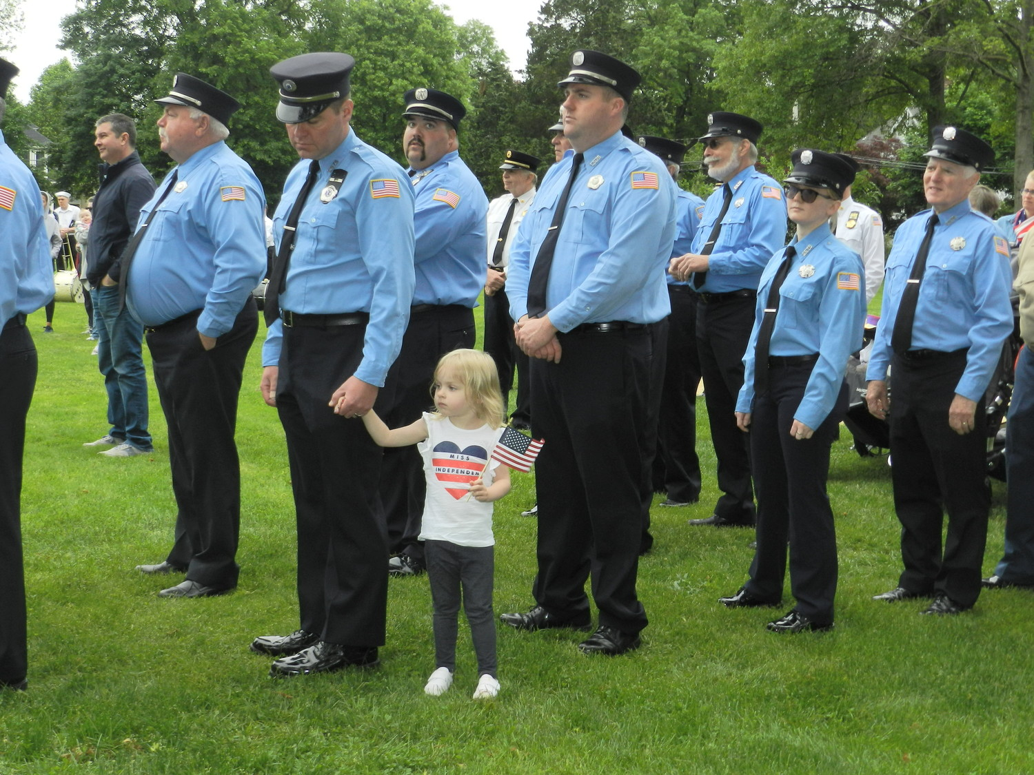 Evelyn Pierce, 3, held tight to her father's hand during the invocation ceremony at the Sea Cliff Memorial Day parade. Christopher Pierce and his father Jack, to his right, are both members of the Sea Cliff Fire Department.