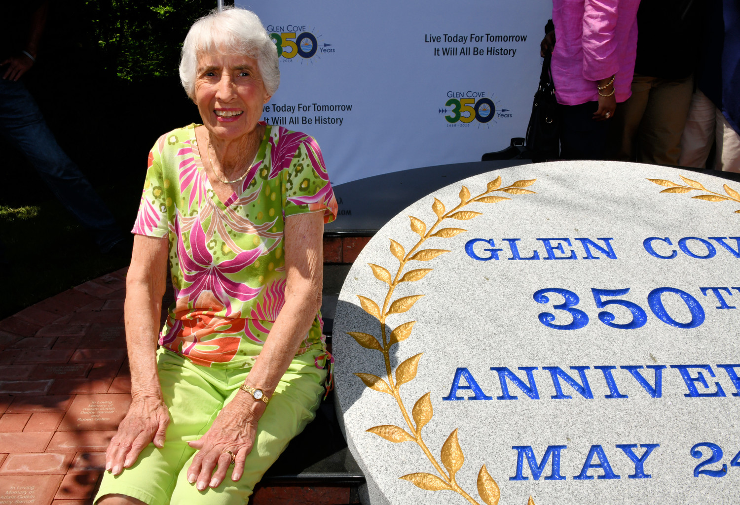 Barbara Coles Schiraldi, a descendant of one of Glen Cove's founding families, sat next to the new 350 monument below at Mill Pond.