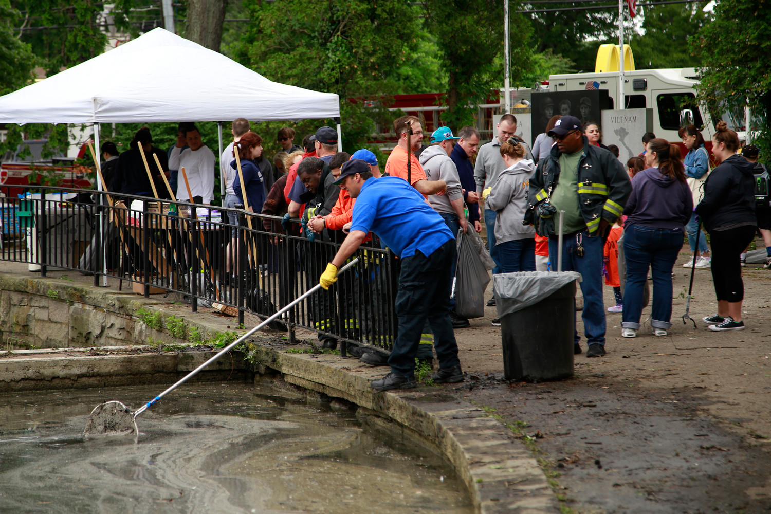 Lakeview Fire Department Ex-Chief Vic Cantelmo skimmed the pond for debris during the cleanup last Sunday.