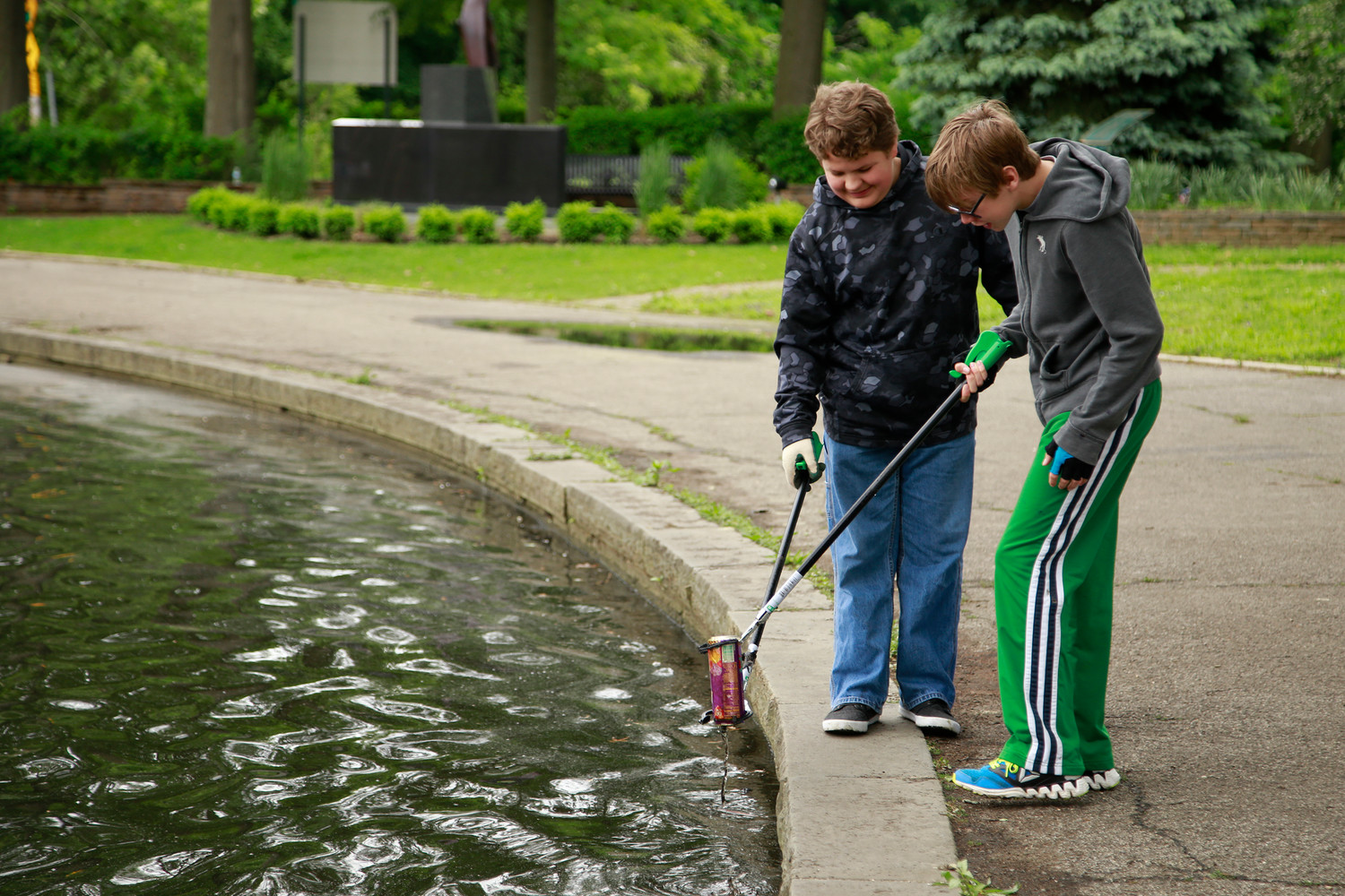 Boy Scouts KJ Fork, 13, left, and Dennis Kavanaugh, 14, removed trash from  the pond.