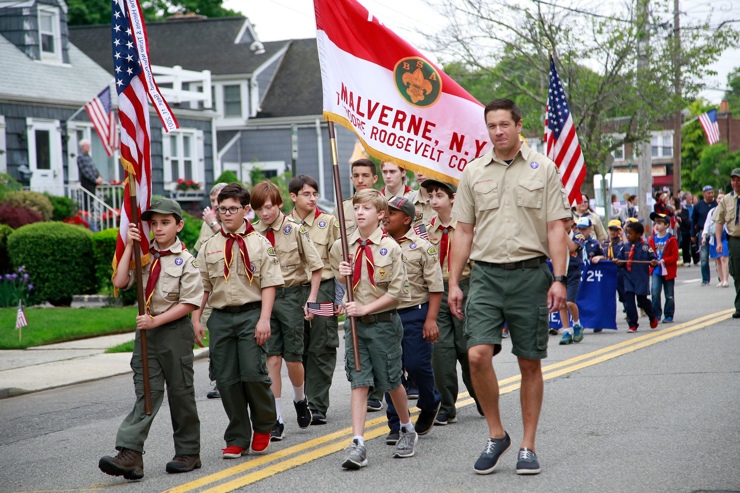 Carl Prizzi, right, led Boy Scout Troop 24 of Malverne at the parade.