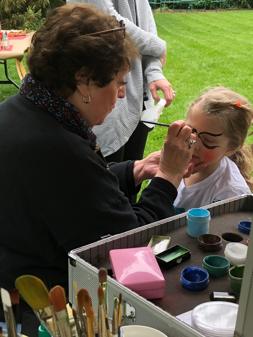 Raynham Hall's JoAnn Alario-Paulsen ensured that children like Claire Kane, 4, were happy with the designs she created with face paint.