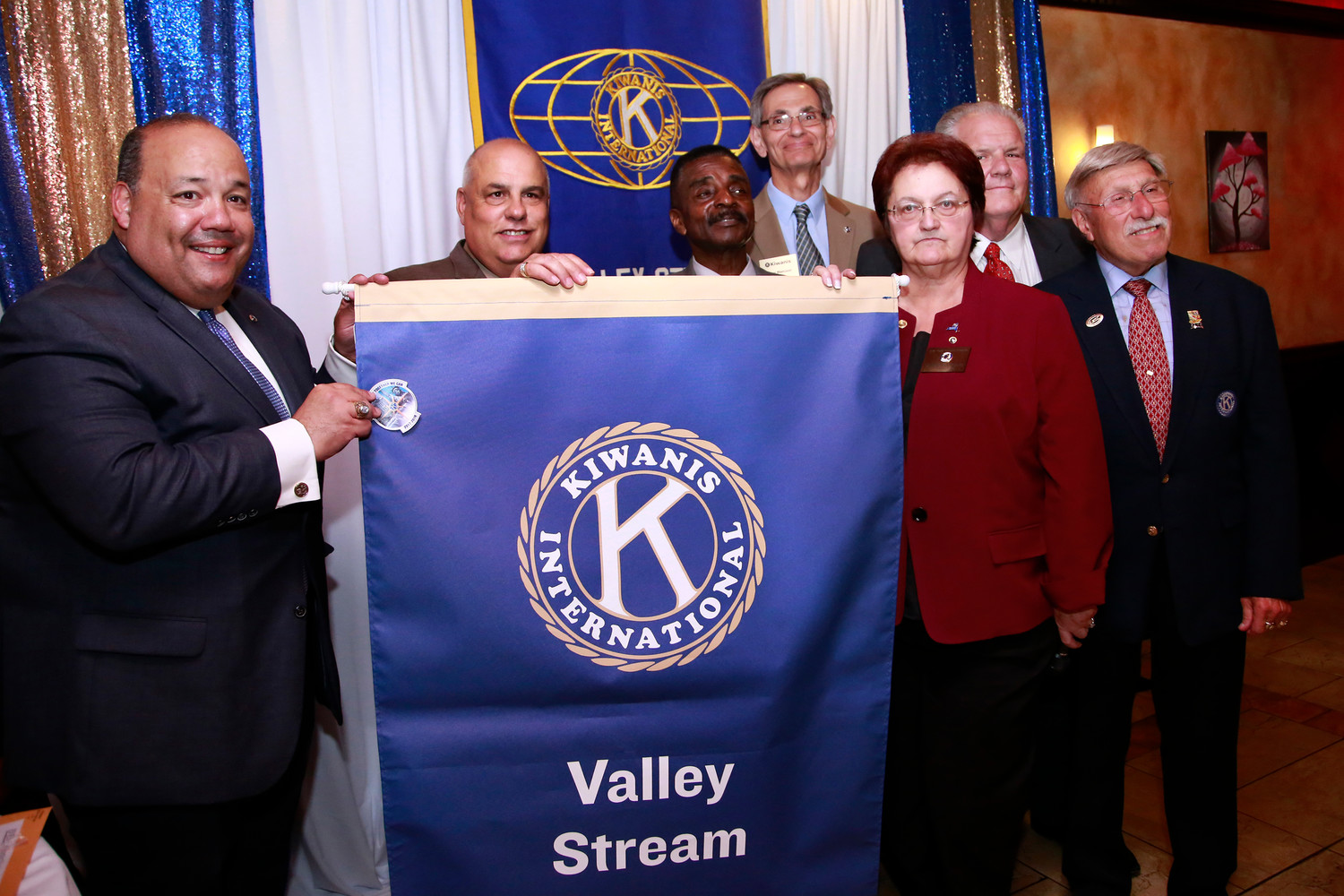 President Richard Ramos and NY District Governor Candace Corsaro hold the V.S. Kiwanis banner.