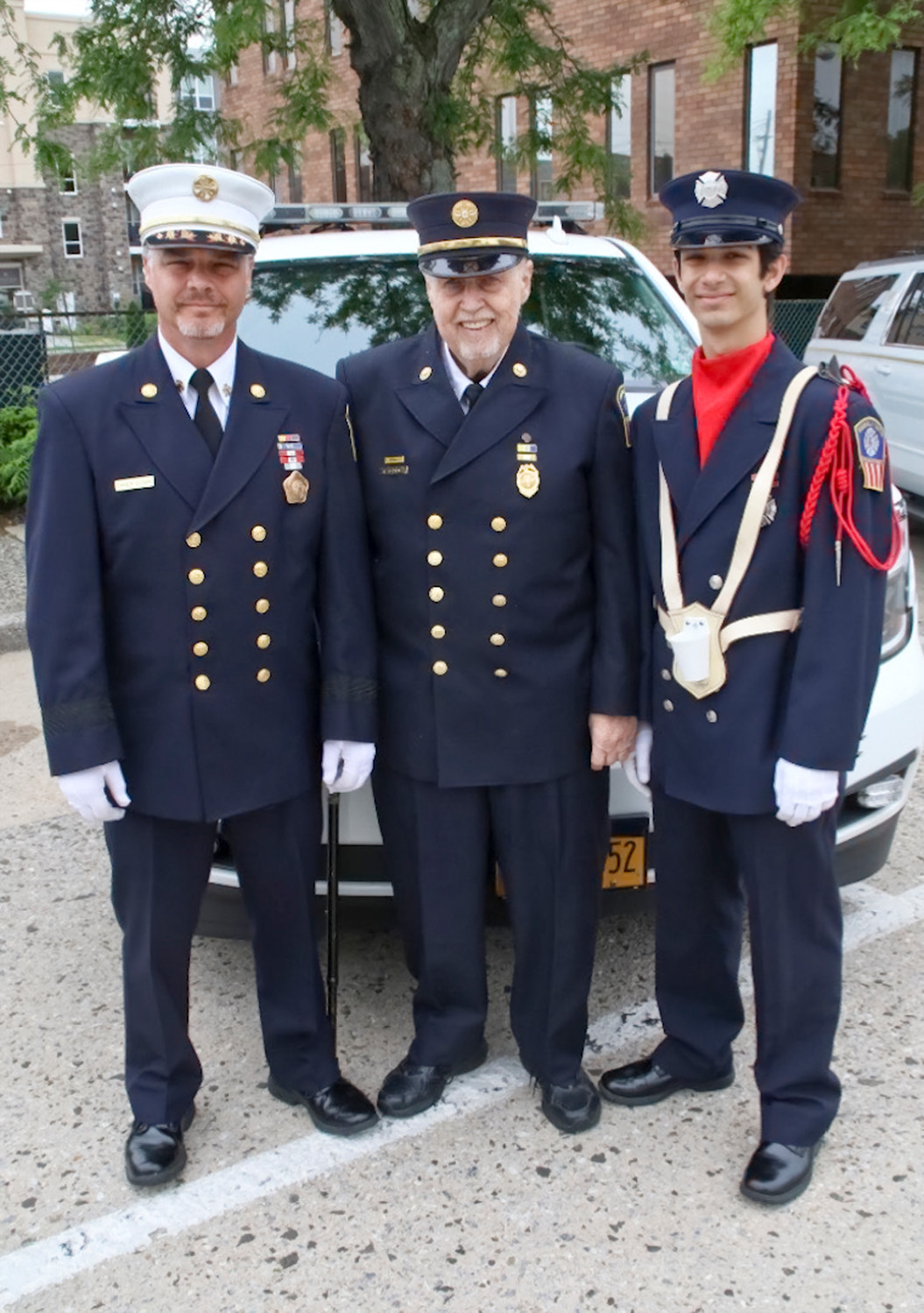 Rockville Centre Fire Department Chief Brian Cook, left, his father, Tom, an honorary chief, and his son, Johnny, a probationary firefighter, attended the Memorial Day Parade on May 28.