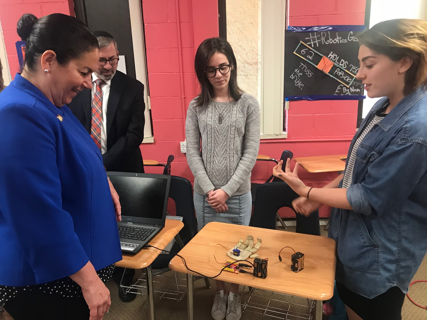 Assemblywoman Stacey Pheffer Amato, far left, and Rabbi Zev Friedman watched Leah Rubin, far right, show the robotic hand that she and Tal Gaon, center, built.