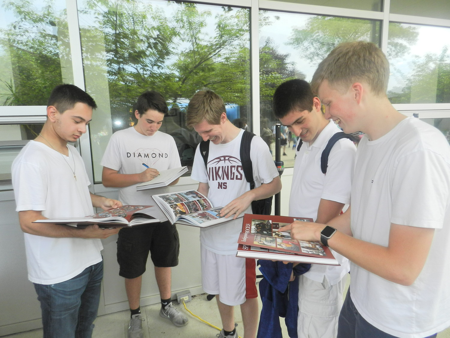 Graduating seniors Jacob Moran, left, Eric Rubenacker, Eric Lynch, Scott Klein and Jack Stalzer took a moment to reflect on their time at North Shore as they signed each other's yearbooks.