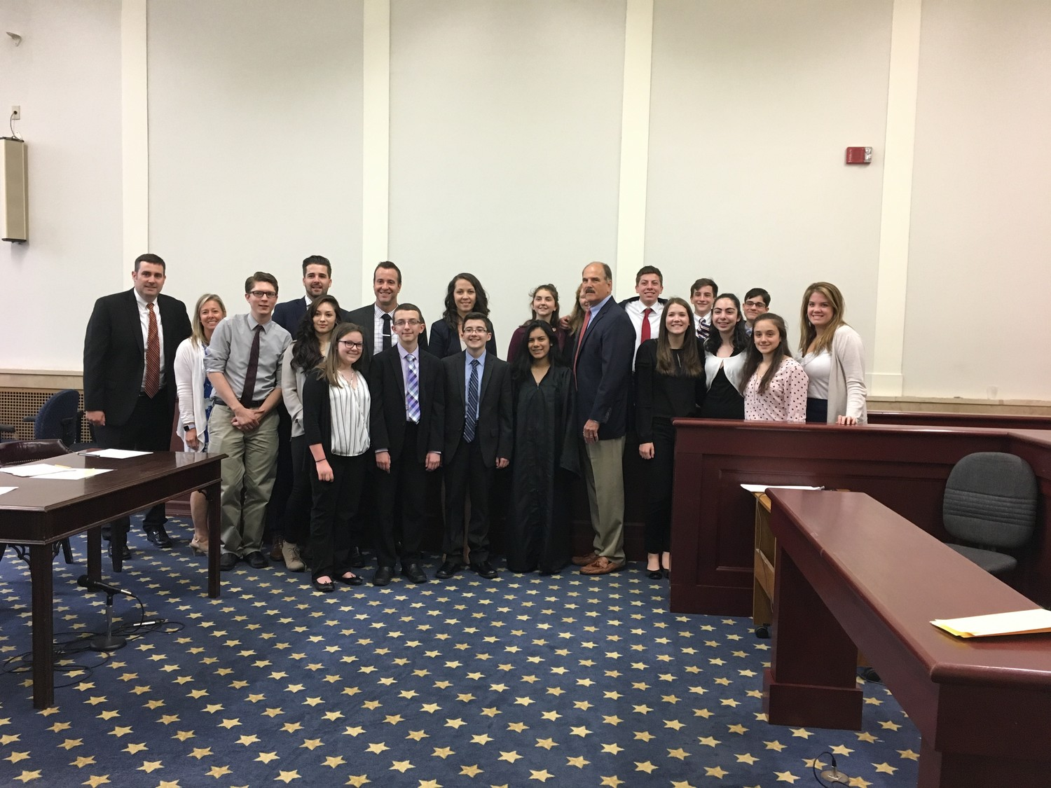 Participants in the Glen Cove Youth Court program, along with their adult advisors, gathered for a pre-trial photo in the Glen Cove City Courthouse, where young jurors found that it was the defendant's mother, and not the defendant, who let the dogs out.