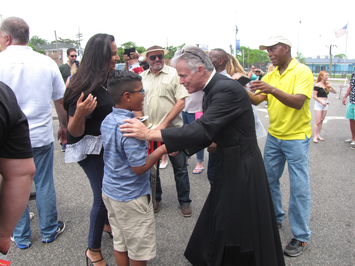 Elijah Espinal, 9, near right, greeted the Rev. Douglas Arcoleo after the festival's ribbon-cutting ceremony.