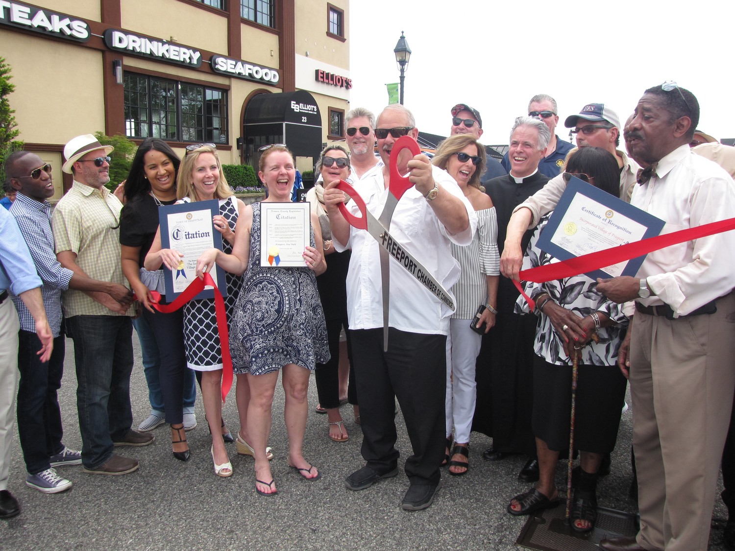 Mayor Robert Kennedy, center, cut the ribbon to officially kick off the 32nd Nautical Mile Festival and the seventh annual Blues Festival on June 2 in Freeport.