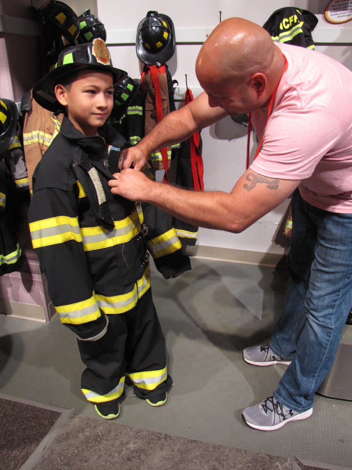 Freeporter Luis Marin, left, helps his third grader, Dylan Marin, 8, get into the turnout gear available for children to try on at the Nassau County Firefighters Museum and Education Center during the Bayview Avenue visit to the museum.