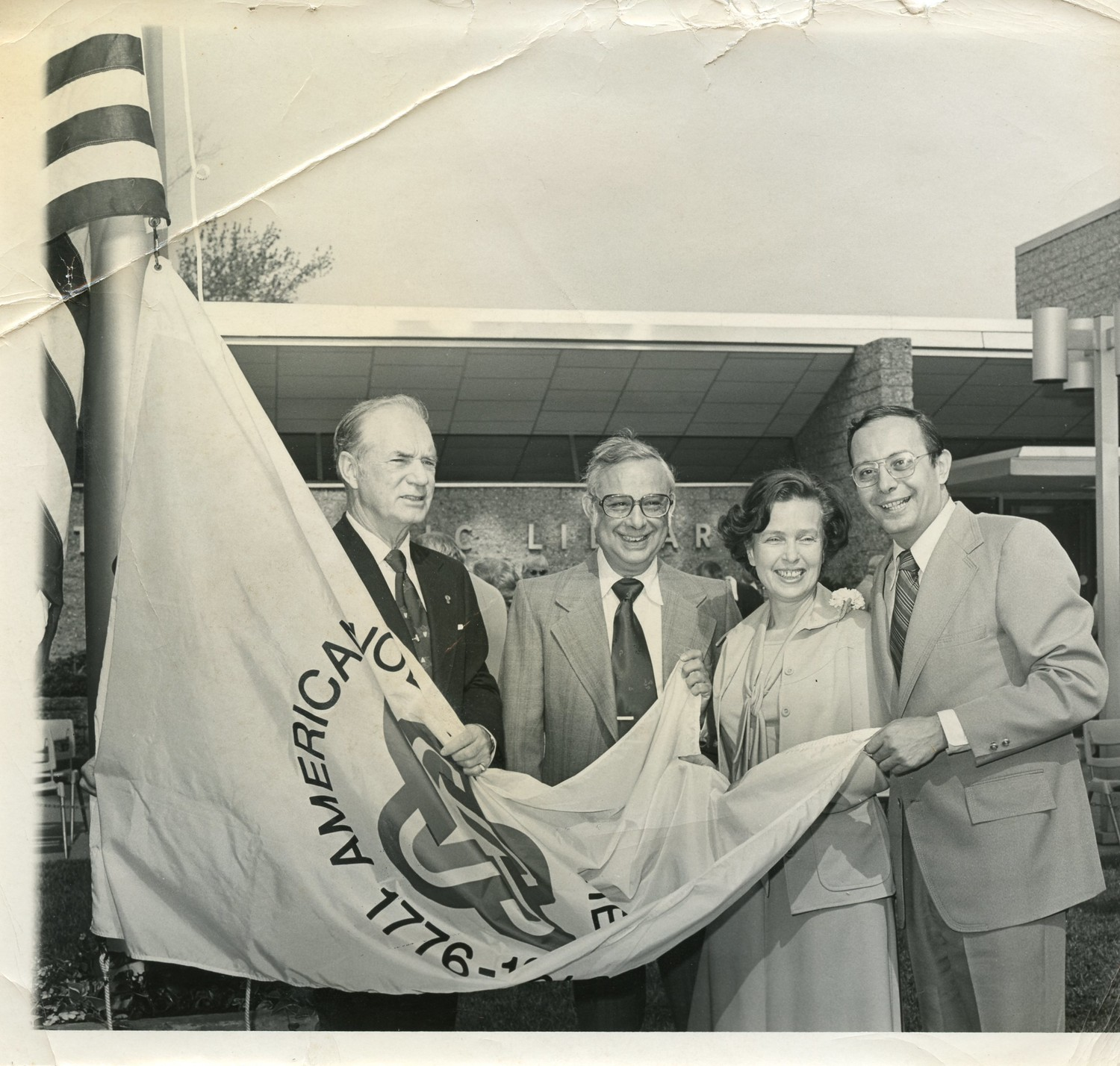 Donna Rigali stands next to then Hempstead Town Supervisor Alfonse D'Amato, as a Bi-centennial flag is presented to the Wantagh Library in 1976.