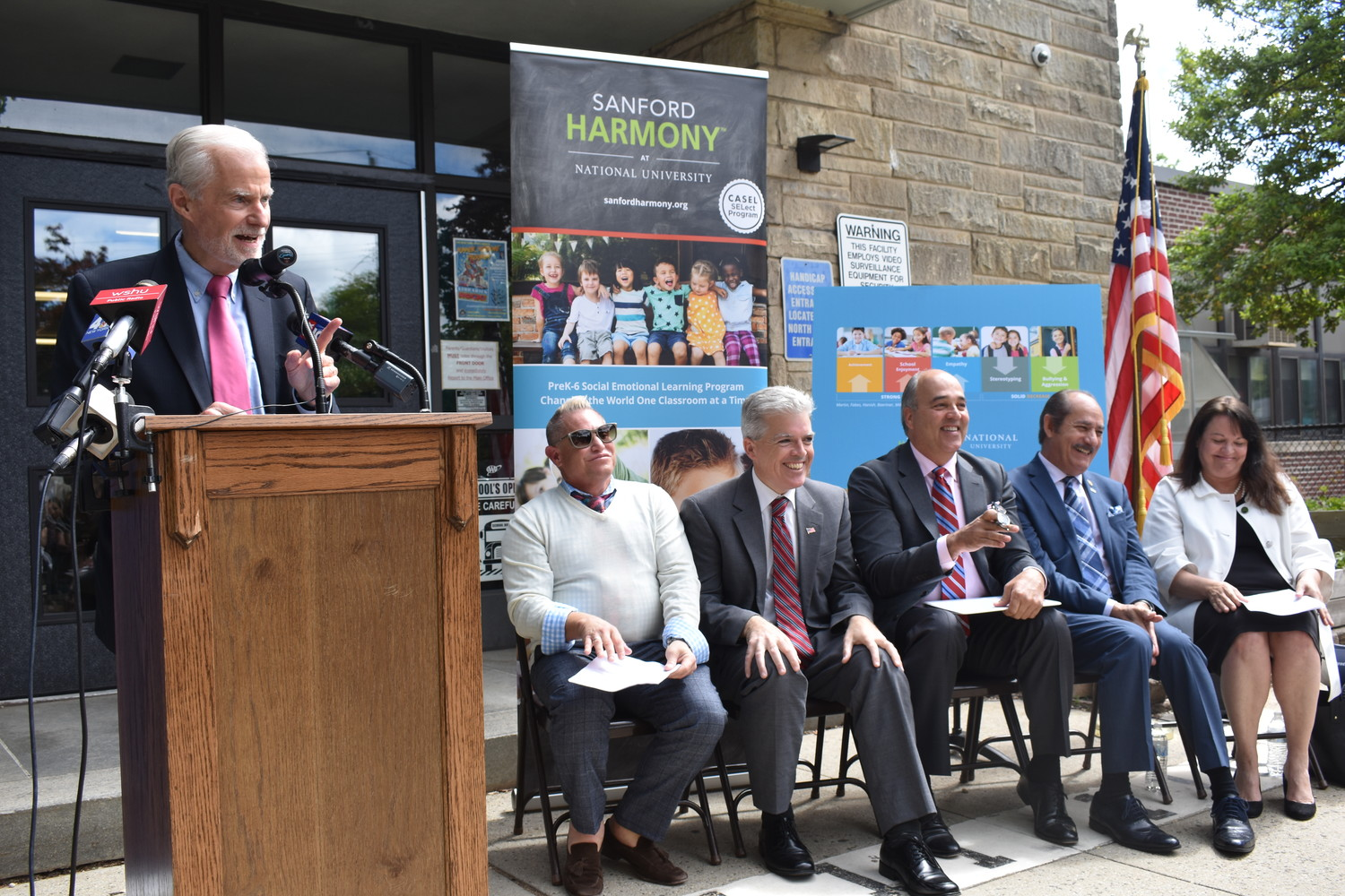 Schools Superintendent Dr. William Johnson lauded Sanford Harmony. Seated, from left, at the donation announcement were Covert Elementary School Principal Darren Raymar; Suffolk County Executive Steven Bellone; Dr. Michael R. Cunningham, chancellor of the National University System; Guillermo Linares, acting president of the Higher Education Services Corp.; and Kimberly Cline, president of Long Island University.