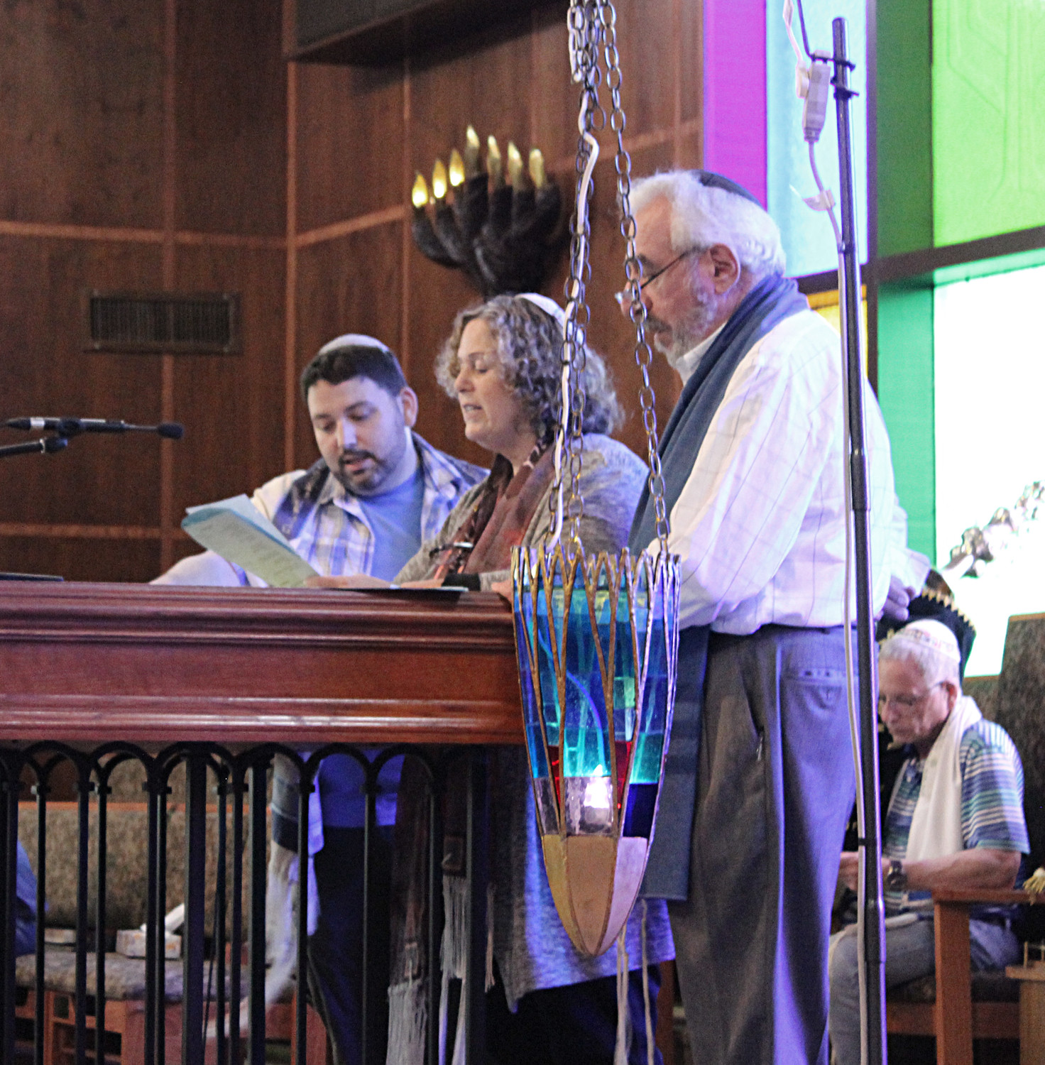 "When the congregants of Temple Emanu-El reached their new home at Temple B'nai Torah, their leaders, Rabbi Daniel Bar-Nahum, left, Cantor Rica Timman and Rabbi Howard Nacht, surprised them by lighting their ""eternal flame."""