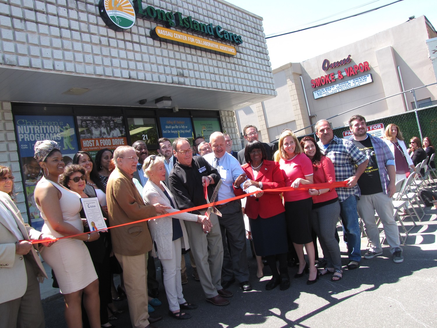 Paule Pachter, CEO, center, of the nonprofit Long Island Cares, cut the ribbon on the organization's new food pantry on Sunrise Highway in Freeport on June 12. Joining him were Sandra Chapin, to his right, widow of LIC founder Harry Chapin, and a host of local leaders.