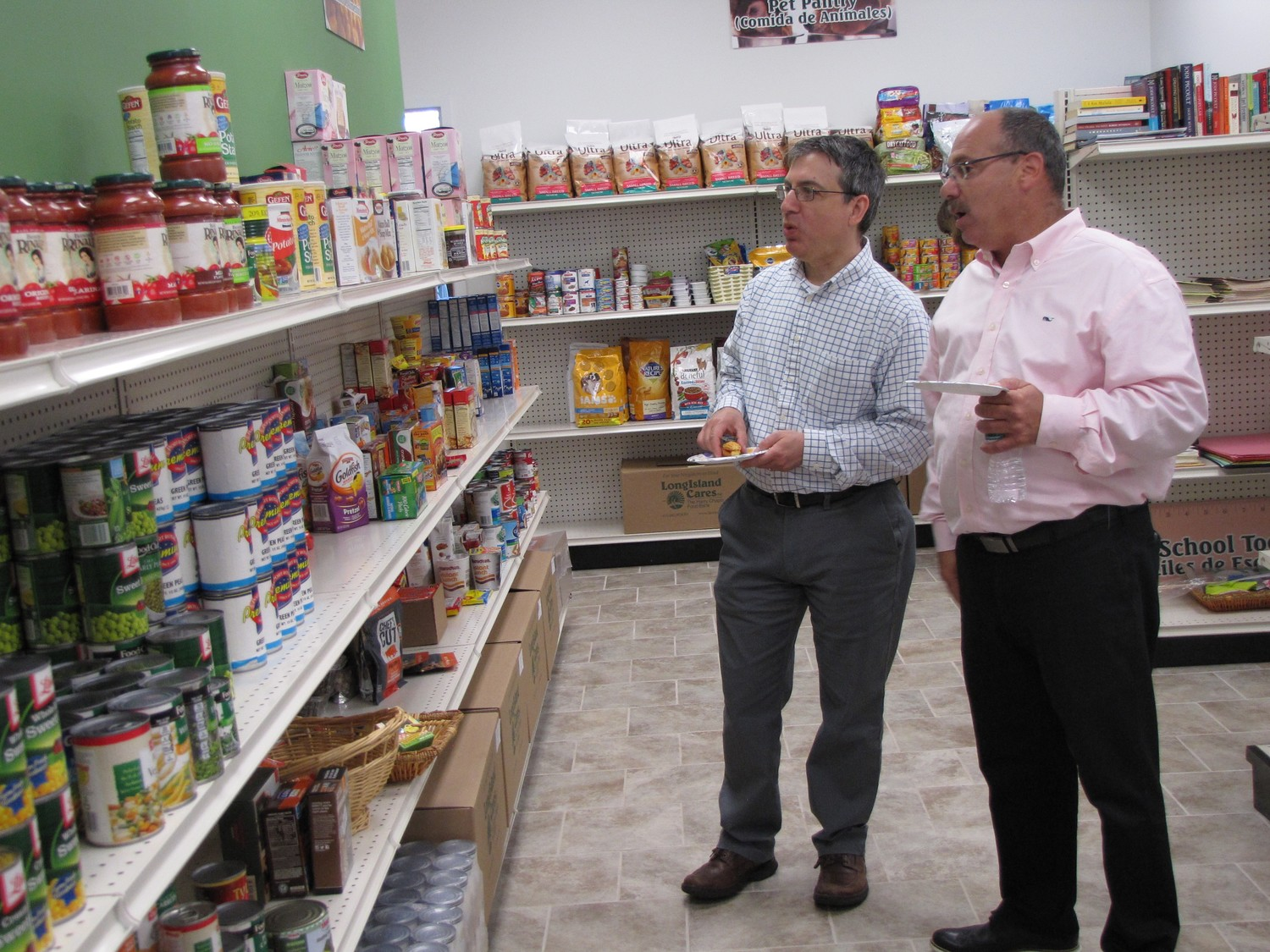 Robert Goldeber, left, and Vincent Marion, owners of Signarama in Hicksville, toured the new Long Island Cares office after the ribbon cutting.