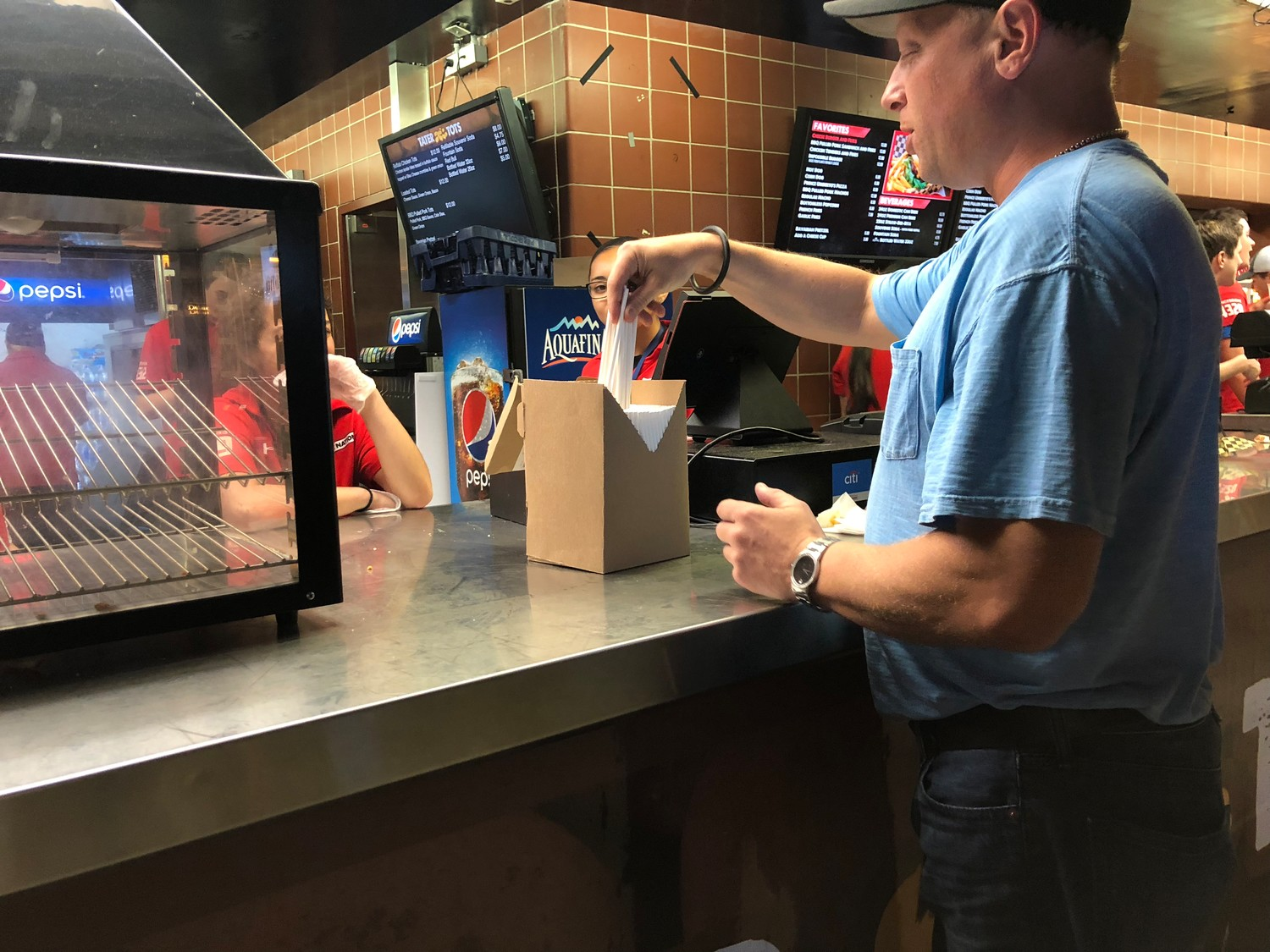 Adam Citron, general manager of the Northwell Health at Jones Beach Theater, handed paper straws to a worker at one of the concession stands.
