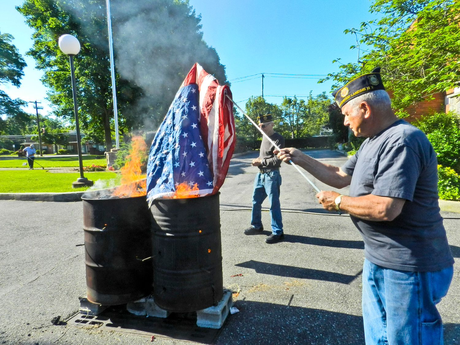 Korean War veteran Rocco Douso hoisted an American flag into the fire during the ceremony.