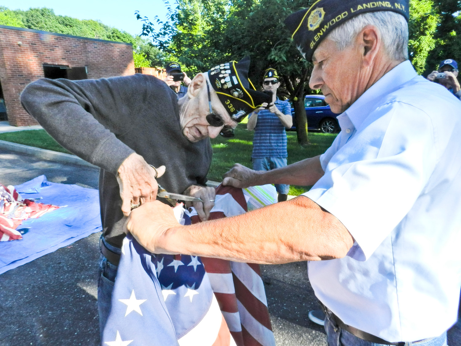 Veteran Richard Hartney, left, of Sea Cliff, cut the stars from an American flag during the American Legion's annual flag burning ceremony last Saturday, assisted by Post 336 Commander William Laderer.