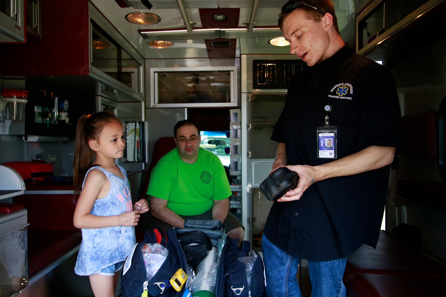 Chris Harran and Michael Pietroburgo give 6-year Lauren Gullotti a tour of an ambulance.