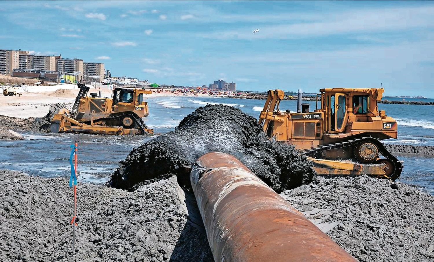 A previous sand-replenishment project in Rockaway Beach in 2013, pictured, shows the process of hydraulically pumping sand onto the beach.