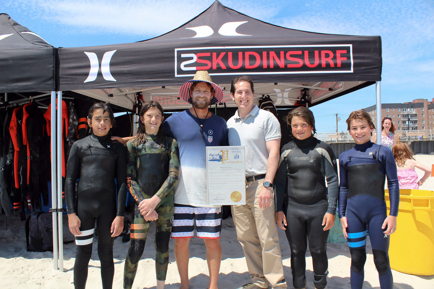 Pro big-wave surfer Will Skudin, third from left, was honored by State Sen. Todd Kaminsky, center, for making the 2018-19 World Surf League's Big Wave World Tour.