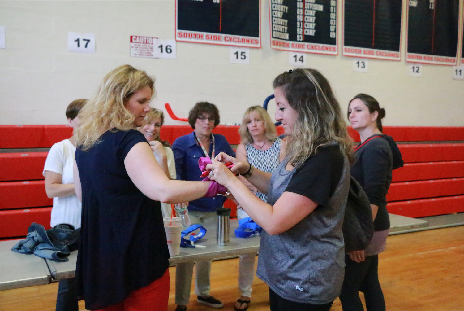 South Side High School staff members Emily Santamarina and Tara McElynn practice applying tourniquets as part of the Stop the Bleed training administered by the Northwell Health Trauma Institute on June 21.