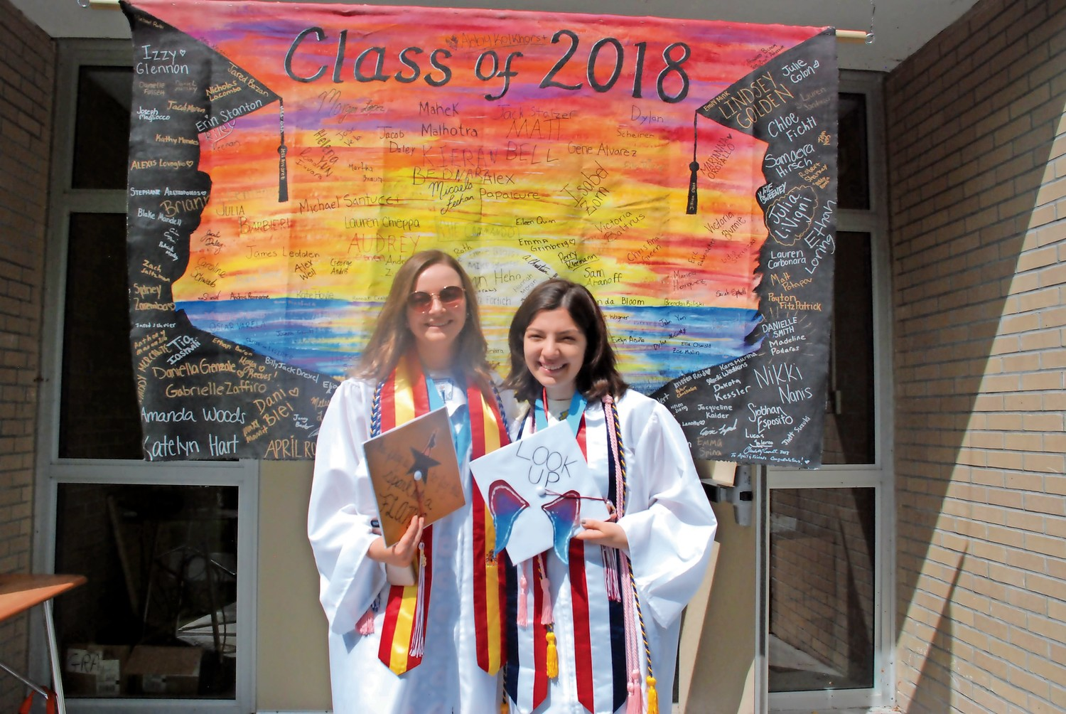 Siobhan Esposito and Caroline Schwab with the senior banner before the rest of the class took the field for commencement. The two led the crowd in singing North Shore's alma mater.