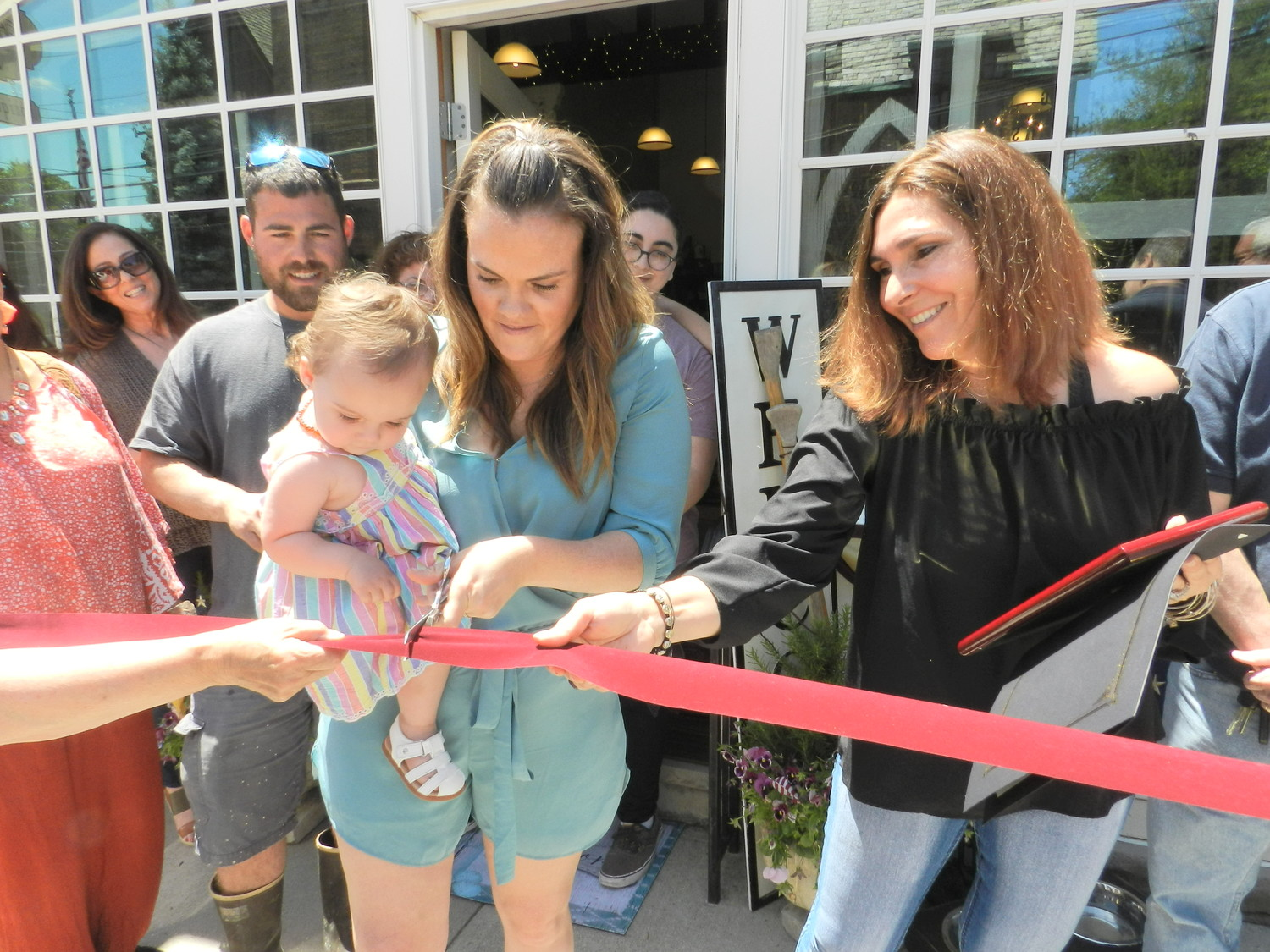 Proprietor Lisa Marchetti, right, let her granddaughter Sailor do the honors of cutting the ribbon at the grand opening of her store My Beautiful Mess.