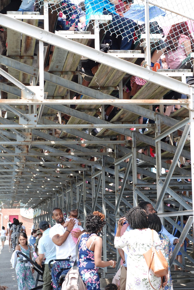 Some families took shelter from the sun under the bleachers.