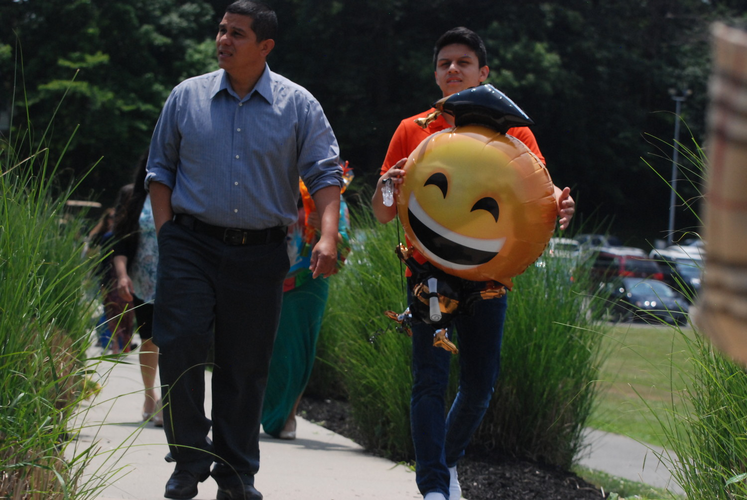 Rolando and Jose Molina brought an inflatable emoji honoring   graduate Wendy Molina.