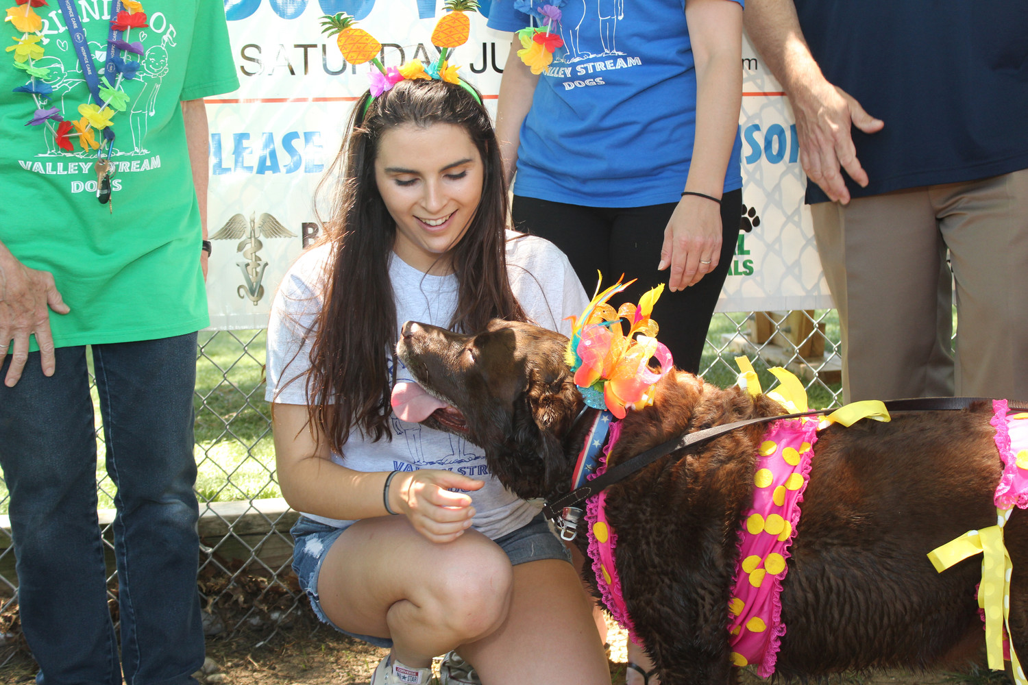 Sara Pergola, right, a volunteer with Friends of Valley Stream Dog Park, got a hug from Bella, a Labrador, at the Bow Wow Luau held at the Valley Stream Dog Park.